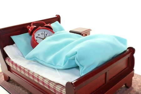 arousing: Sleepy - alarm clock in bed with bedside and blue bedding Stock Photo