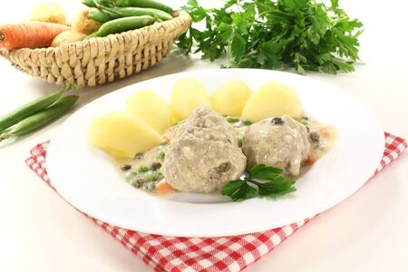 cooked meatballs in a white sauce with capers, vegetables and potatoes on a light background photo