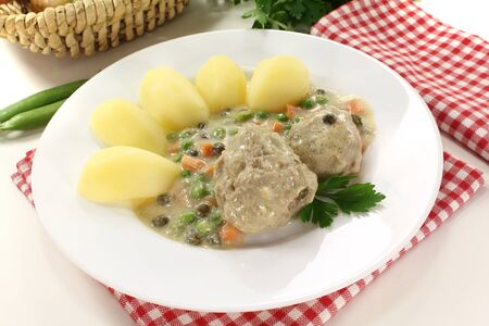 delicious cooked meatballs in a white sauce with capers, potatoes and parsley on a light background photo