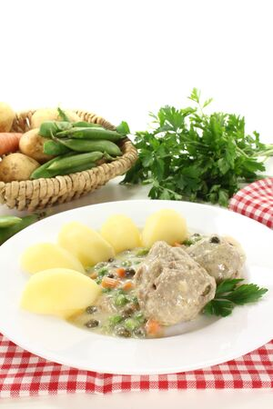 fresh cooked meatballs in a white sauce with capers, carrots and potatoes on a light background photo