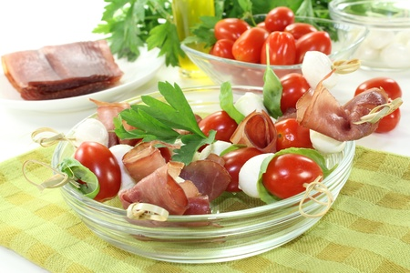 fresh Tomato, mozzarella and ham skewers with basil on a napkin before light background photo