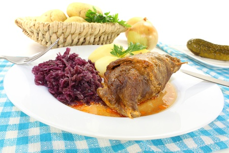 fresh roasted beef roulade with potatoes and red cabbage on a bright background photo
