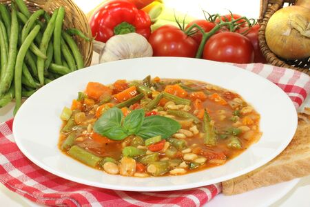 minestrone: Minestrone with green beans, carrots, potatoes and leeks on a light background