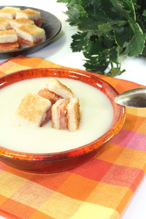 fresh Cream of celery soup with salmon croutons on a checkered napkin before light background photo