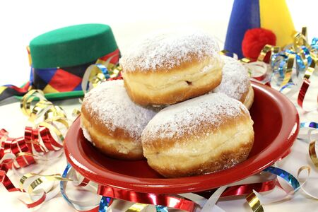 baker's: Pancakes with powdered sugar and jam on a plate with paper streamers and carnival hats Stock Photo