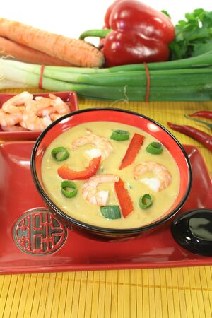 Curry soup with shrimp, red pepper, leeks and coconut milk on bright background photo