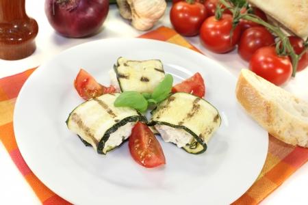 amuse: fresh stuffed zucchini rolls with cream cheese on a light background