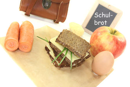 recess: sandwich eaten during recess with egg, carrots and apple on a bright background Stock Photo