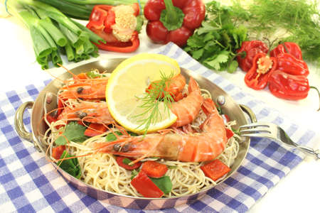 mie noodles: Prawns with mie noodles, lemon, bell pepper, dill and coriander on a light background Stock Photo