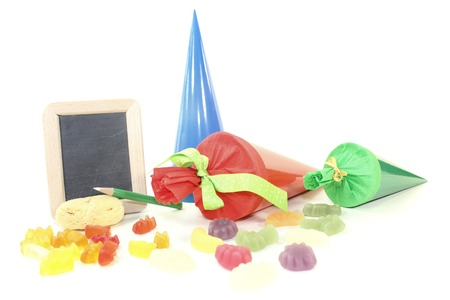 School bag with pen, sponge, blackboard and sweets on a light background photo