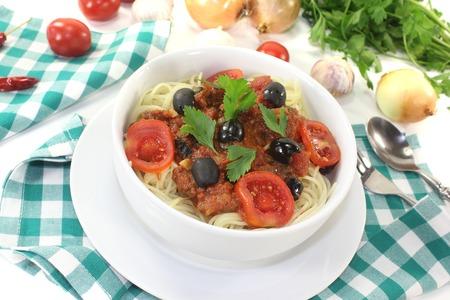 puttanesca: Spaghetti alla puttanesca with tomatoes on light background Stock Photo