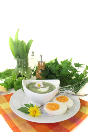 dollop: green herb soup with eggs, a dollop of cream and daisy Stock Photo