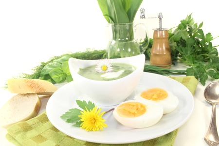 dollop: green herb soup with boiled eggs, a dollop of cream and daisy