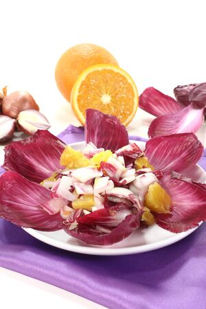 slightly: red chicory salad with orange slices and dressing Stock Photo