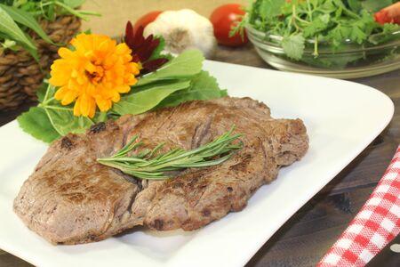 carnes y verduras: Entrecot fresco y ensalada de hierbas silvestres con romero Foto de archivo