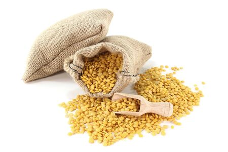 yields: dried yellow lentils in sacks with bushels on a light background Stock Photo