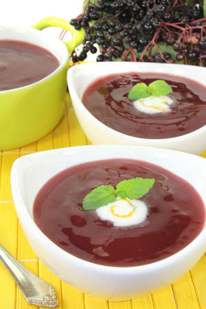 dollop: elderberry soup with dollop of whipped cream and mint on a light background