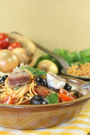 puttanesca: Spaghetti alla puttanesca with capers and anchovies on a napkin