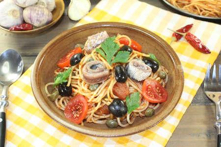puttanesca: Spaghetti alla puttanesca with olives, capers and anchovies on a napkin