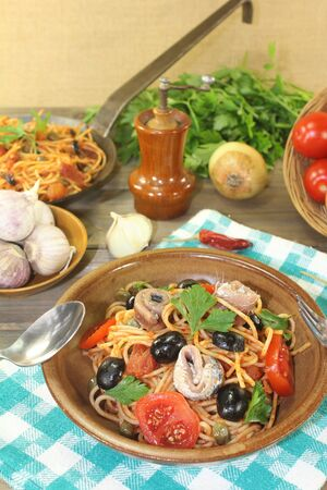puttanesca: Spaghetti alla puttanesca with olives and capers on a napkin