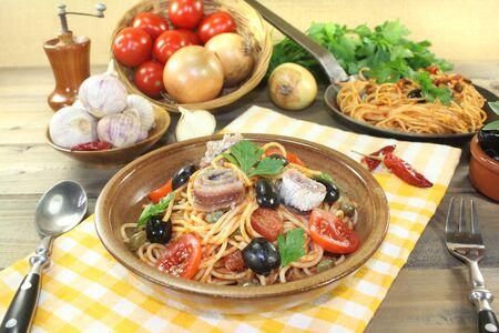 puttanesca: Spaghetti alla puttanesca with capers and tomatoes on a napkin