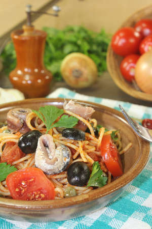 puttanesca: Spaghetti alla puttanesca with anchovy and tomatoes on a napkin