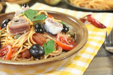 puttanesca: Spaghetti alla puttanesca with olives and tomatoes on a napkin Stock Photo