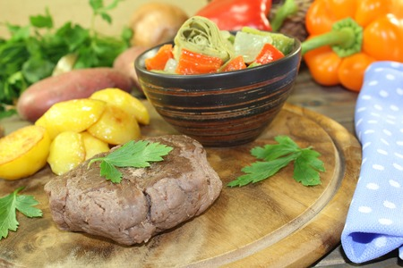 baked potatoes: Ostrich steaks with baked potatoes and parsley on a wooden board Stock Photo
