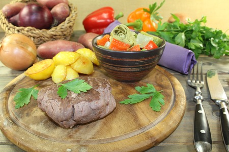 baked potatoes: Ostrich steak with crispy baked potatoes and parsley on a wooden board Stock Photo