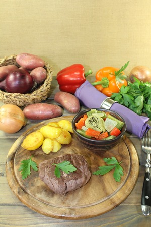 baked potatoes: roasted ostrich steaks with baked potatoes and vegetables on a wooden board