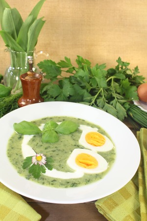 dollop: fresh green herbs soup with eggs and a dollop of cream