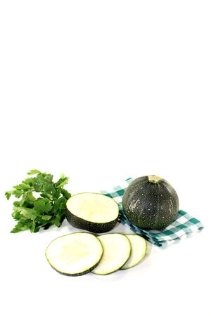 globular: rotund raw zucchini on a green napkin on bright background