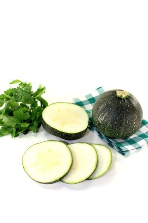 rotund: rotund raw zucchini on a checkered napkin on light background
