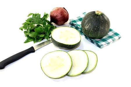 rotund: rotund raw zucchini with onion on a light background