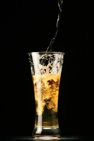 Beer pouring into glass isolated on black background photo