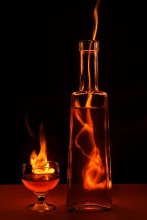 Bottle and glass in flame isolated on black background photo