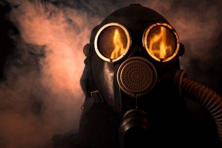 riesgo biologico: Hombre de la m�scara de gas con fuego reflexi�n a los ojos Foto de archivo