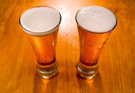 Two beer glasses on wet wooden background, soft focus  photo