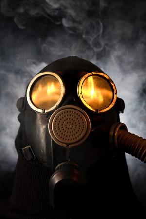 riesgo biologico: Hombre de la m�scara de gas con fuego en la reflexi�n sobre los ojos de humo de fondo Foto de archivo
