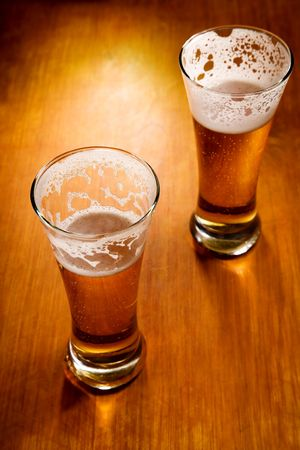 Two beer glasses on wood background, selective focus   photo