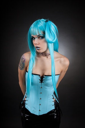 Cyber gothic girl with creative makeup wearing contact lenses and false eyelashes, in blue vinyl outfit Stock Photo - 8764401