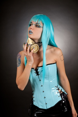 Cyber gothic girl in glamour gas mask wearing contact lenses and false eyelashes, in blue vinyl outfit  photo