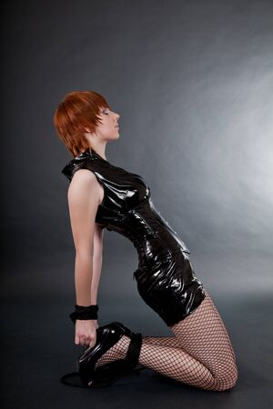 Bondaged woman in fetish outfit, studio shot  photo