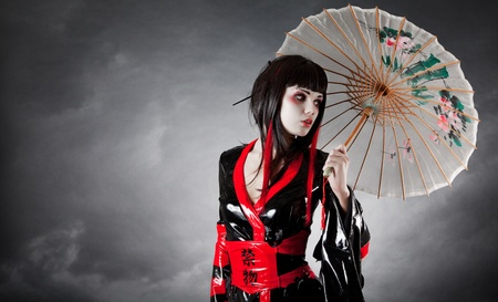 Modern style geisha in fetish kimono with umbrella, studio shot Stock Photo - 8942111