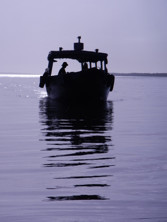 Silhouette fisherman in a boat at sunset Suriname photo