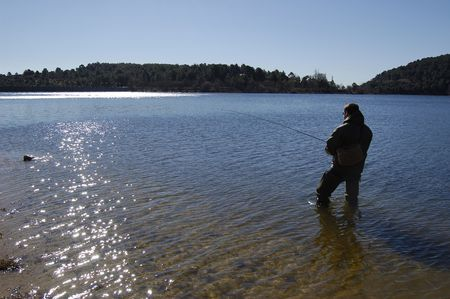 Fisherman fishing on a lake photo