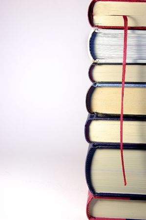 Stack of Books in a tower with a red bookmark in a silver background