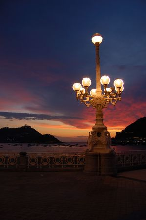 Miraconcha Avenue in San Sebastian at twilight. Spain. Santa Clara Island and Igeldo Castle in background. Stock Photo