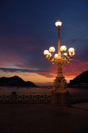 Miraconcha Avenue in San Sebastian at twilight. Spain. Santa Clara Island and Igeldo Castle in background. Stock Photo