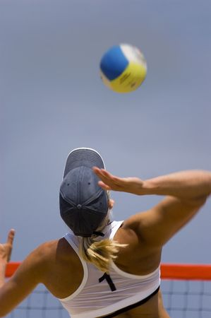Young girl playing volleyball in the beach